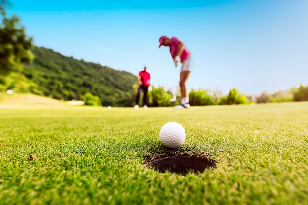 Golfer фокус положить мяч для гольфа в отверстие во время заката, концепция здорового образа жизни.