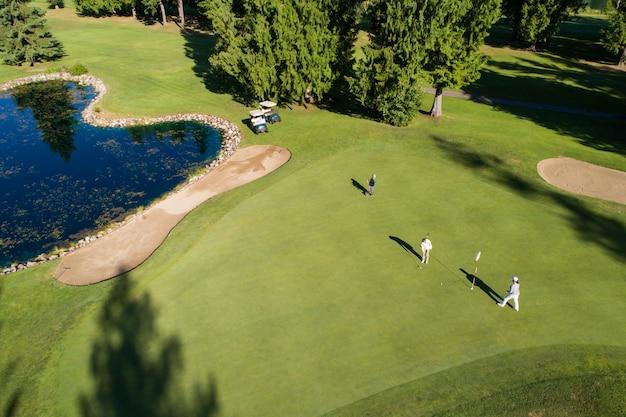 Игроки в гольф на красивом поле для гольфа в солнечный день
