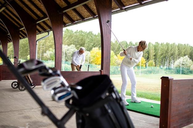 골프 코스에서 롱샷을 연습하는 골퍼.