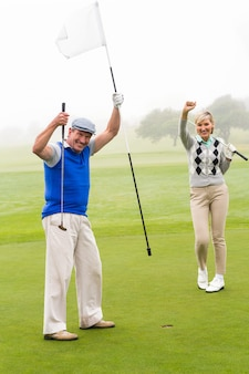 Golfing couple cheering on the putting green
