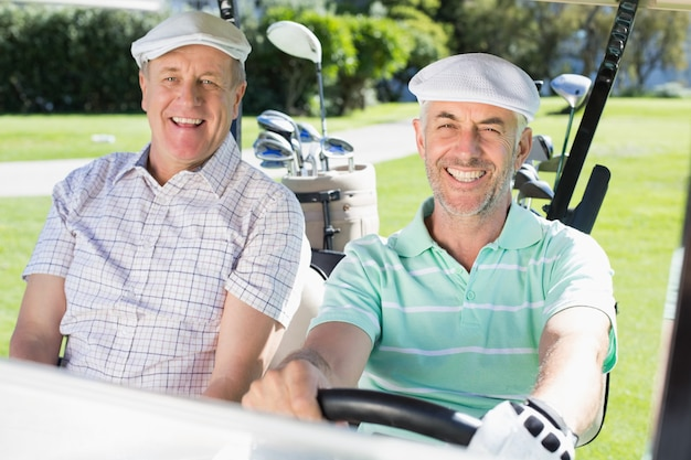Golfing friends driving in their golf buggy smiling at camera