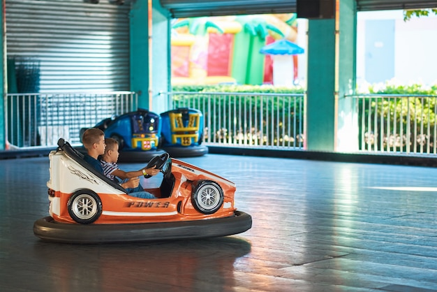 Gomel, belarus - august 22 2019: two boy have fun in a bumper car at amusement park