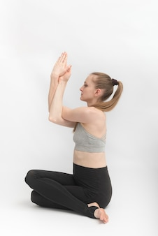 Gomukhasana. cow face pose. slender and flexible young woman practices yoga. hatha yoga. side view.