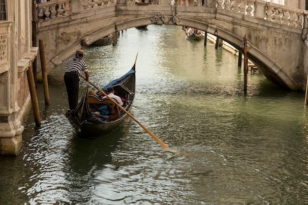 Гондола в венецианском канале проходит под мостом