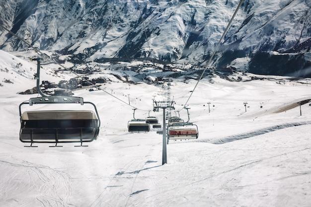 Gondola lift and snow ski slope at sunny day the mountain. caucasus mountains, georgia, region gudauri