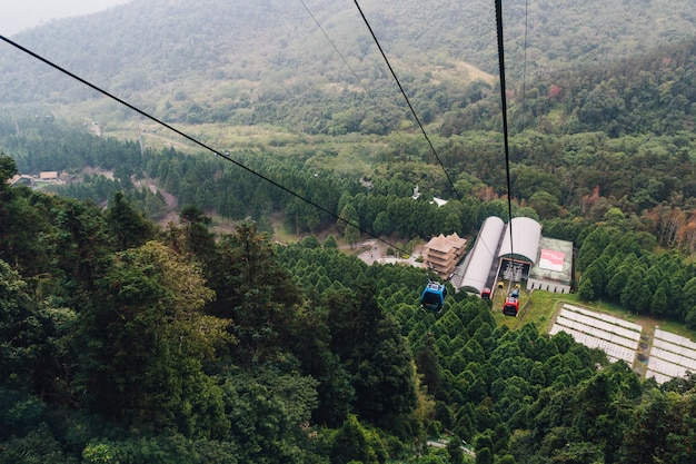 Gondola lifts moving from station over mountain with green trees