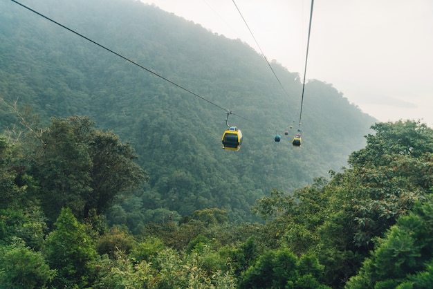 Gondola lifts moving over mountain with green trees in the area of sun moon lake ropeway