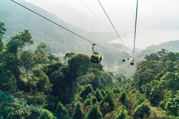 台湾の南投県玉池郷にある日月opeロープウェイのエリアで、ゴンドラが緑の木々に覆われた山の上を移動します。