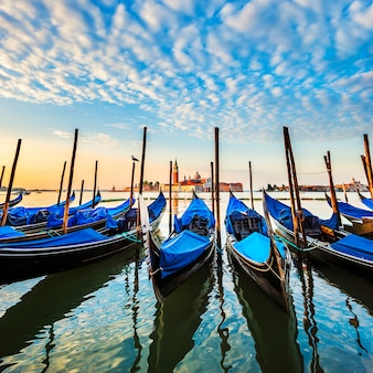 Gondolas in lagoon of venice on sunrise, italy