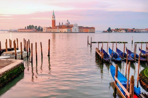 Гондолы пришвартованы напротив сан-джорджо-ди-маджоре в венеции, рано утром, рассвет, розовый свет,