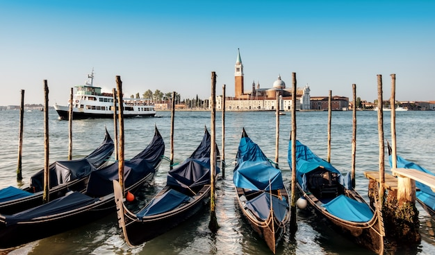 Gondolas moored by saint mark square with san giorgio di maggiore church