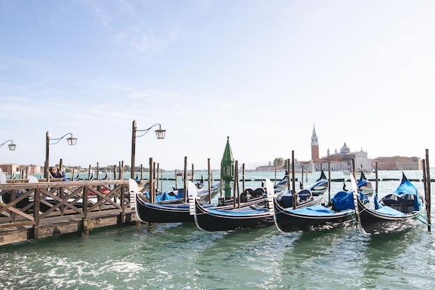 夏、ヴェネツィア、イタリアの明るい日に海の海岸近くのゴンドラ