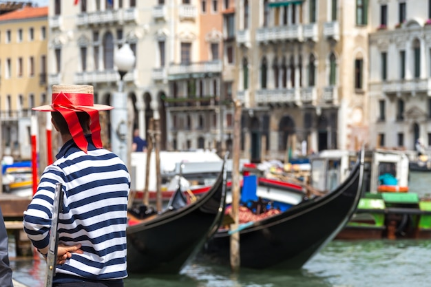 Gondolier standing next to gondola waiting for a client