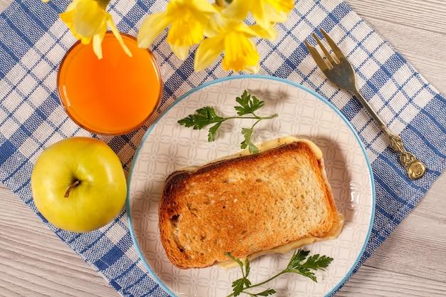朝食のためのおいしくておいしい食べ物と飲み物。フォーク、リンゴ、黄色い水仙の花束、キッチンナプキンにオレンジジュースのグラスを添えた白いプレートにバターとチーズを添えてトーストします。上面図