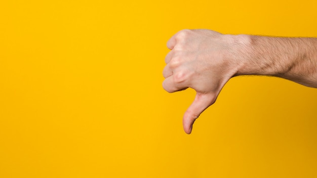 Not good and not approved. close up hand of a man showing thumb down dislike sign  with copyspace for design