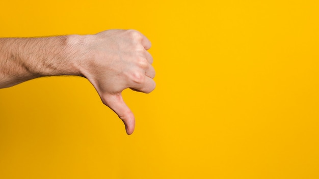Not good and not approved. close up hand of a man showing thumb down dislike sign over yellow background