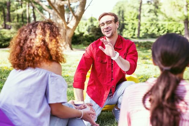 좋은 분위기. 야외에서 작업하는 동안 그의 동료와 이야기하는 즐거운 젊은 남자