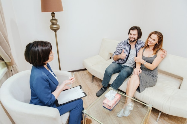 Good and attractive young people are sitting together and embracing each other. they are looking at therapist and smiling. also they are showing their big thumbs up. doctor is looking at them.