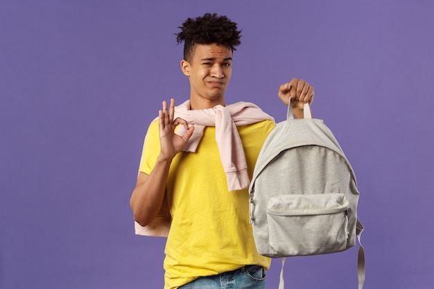 Good but not the best. portrait of disappointed, unsatisfied young teenage student, guy grimacing without enthusiasm show okay, received new ugly backpack, standing purple background