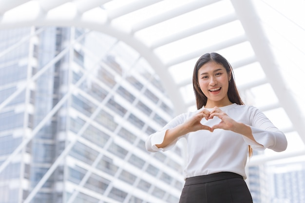 Good business service from heart love care help and support customer working concept.happy woman staff show hand heart shape and smile.
