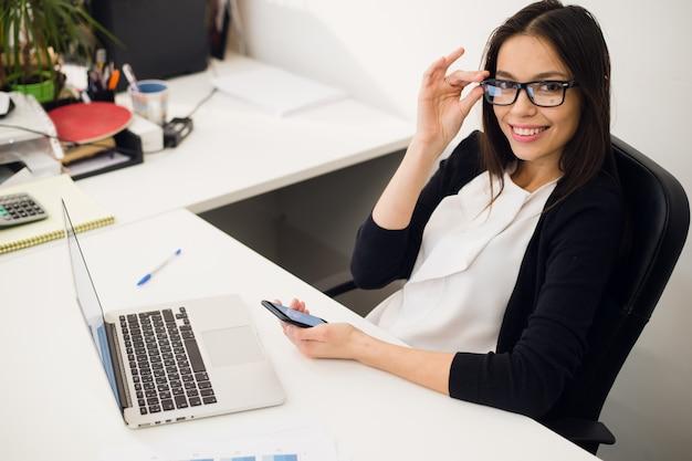 良い商談。携帯電話で話していると彼女の職場に座っている笑顔でラップトップを使用してメガネで陽気な若い美しい女性