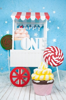 A good cart with the letters one with cakes and sweets.