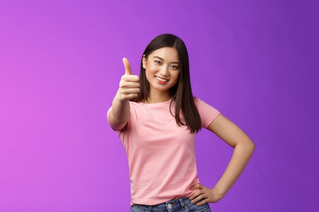 Good choice, well done. pleased happy asian woman in pink t-shirt show thumb-up, approving like your idea, smiling joyfully, accept plan, agree, recommend product, give positive judgement.
