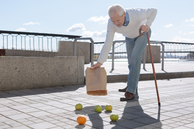 Good clever tired man taking the stick in one hand dropping and emptying fruits on the ground