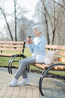 좋은 커피. 벤치에 앉아있는 동안 커피를 마시는 즐거운 금발 여자