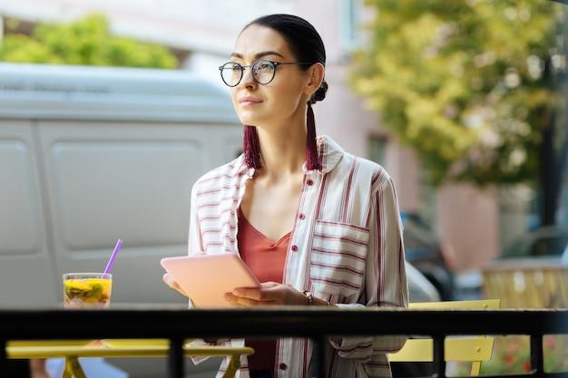 良い一日。カフェテラスに座って、モダンなタブレットを持って笑っている美しい穏やかな女性