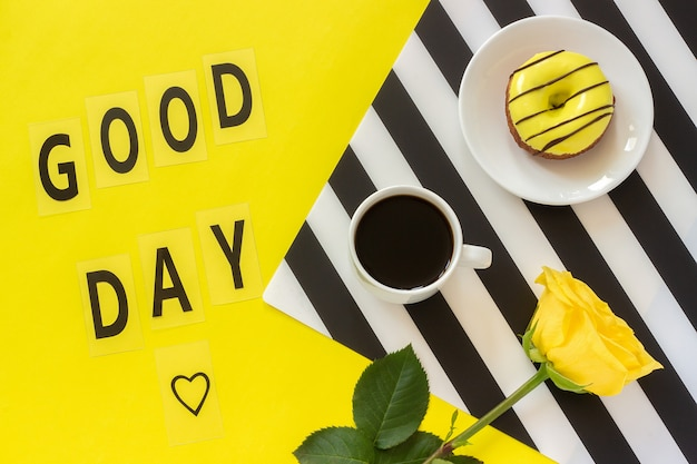 Good day, coffee, donut, yellow rose on stylish black and white napkin on yellow background.