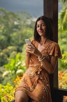 좋은 날. 카메라를 똑바로 바라보면서 스마트폰을 양손에 들고 기뻐하는 여성
