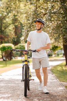 Добрый день. улыбающийся рыжеволосый парень в шлеме и в спортивной одежде с велосипедом гуляет в парке в солнечный день