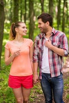 공원에서 산책하기 좋은 날. 공원에서 걷고 손을 잡고 있는 아름다운 젊은 부부