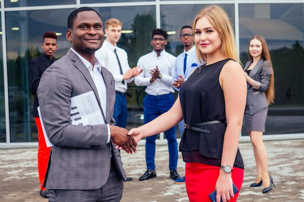 Good deal concept.multinational group of young business people greetings and handshaking with colleagues in the background. beautiful smiling businesswoman with african american partner shaking hand