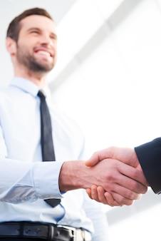 Хорошая сделка! низкий угол обзора уверенного бизнесмена, пожимающего руку своему деловому партнеру и улыбающегося