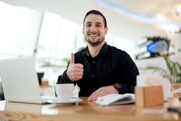 お得!親指を立てて、カメラを見て、笑顔で満足している若いフリーランサー。背景に居心地の良いコーヒーショップ。黒のシャツを着た男は彼の仕事が大好きです。ラップトップとテーブルの上のカプチーノのカップ。