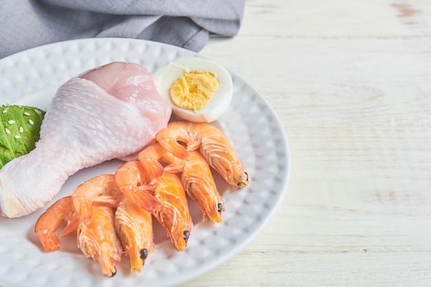 Хорошие источники жира на тарелке - курица, морепродукты, яйцо, авокадо, кунжут. концепция здорового питания и кетогенная диета