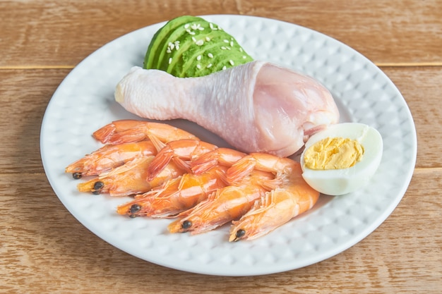 Good fat sources on a plate - chicken, seafood, egg, avocado, sesame. healthy eating and ketogenic diet concept