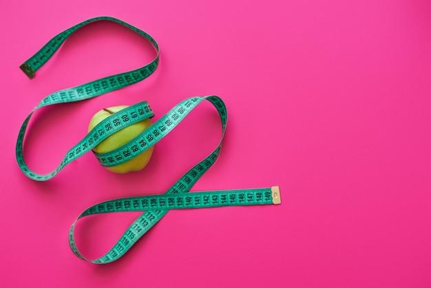 좋은 그림에는 건강한 음식이 필요합니다. 녹색 사과는 분홍색 배경에서 미터를 측정했습니다.