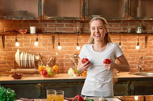 良い食べ物の選択は良い投資です居心地の良いモダンなキッチンで野菜を調理する幸せな若い女性