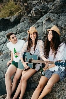 Good friends at the beach with guitar