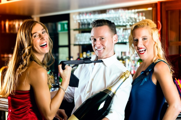 Good friends, bartender and women - with a large magnum bottle champagne at bar having fun, she pulls on his tie