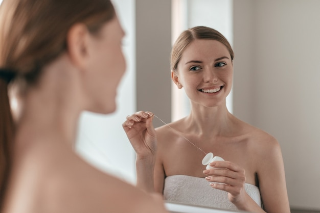 Good habit. over the shoulder view of young beautiful woman holding dental floss and smiling while looking in the mirror