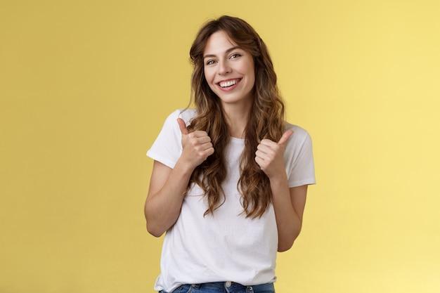 よろしくお願いします。陽気な前向きでかわいい活気のある縮れ毛のヨーロッパの女の子は、ジェスチャーの傾きの頭のような親指を立てる承認を示し、細かい選択スタンドの黄色の背景を判断することを喜んで受け入れます。