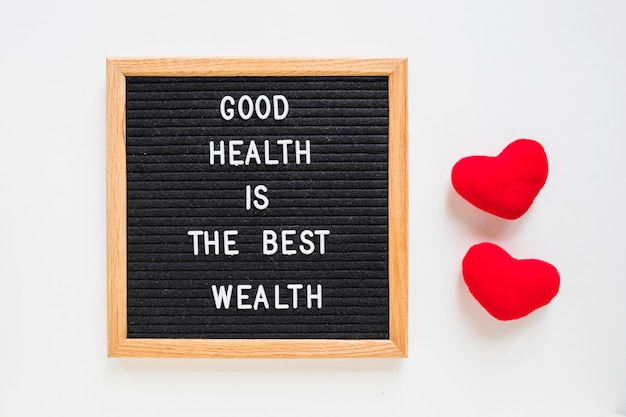 Good health message on black board with stuffed red heart