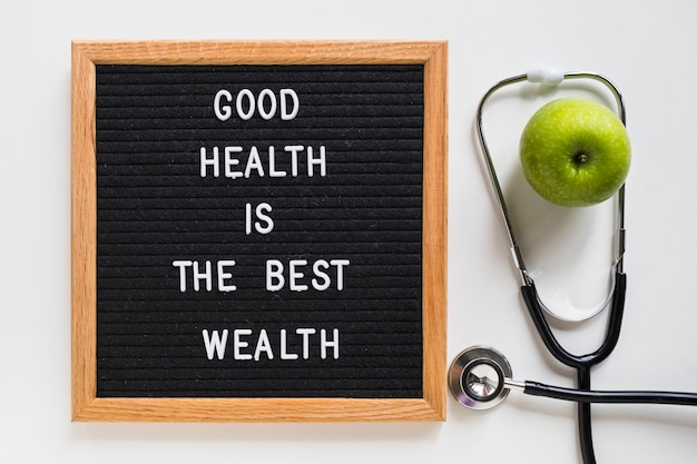 Good health message board with green apple and stethoscope on white background