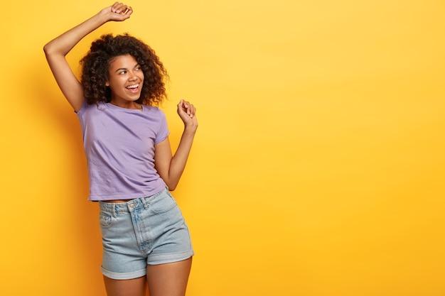 유머러스 한 흑인 슬림 소녀가 노란색 배경에 춤을 추고 행복하게 보이며 캐주얼 한 보라색 티셔츠와 진 반바지를 입습니다.
