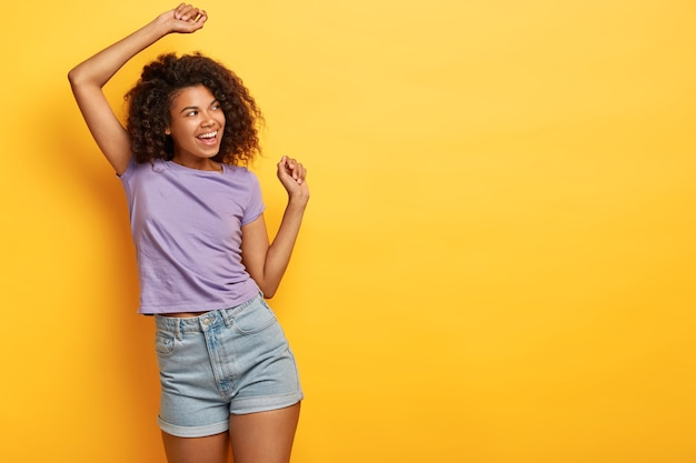 Good humored african american slim girl dances on yellow background, looks happily away, wears casual purple t shirt and jean shorts