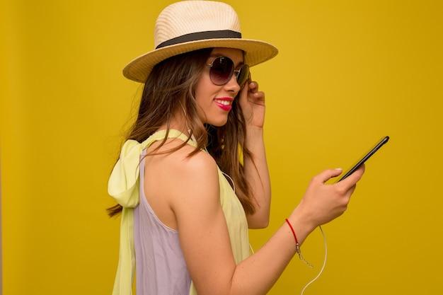 Donna castana di buon umore in abito estivo destro e cappello utilizzando smartphone sulla parete gialla